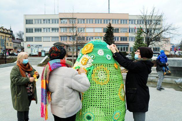 Ilustracja. Ozdabianie wielkanocnej pisanki na skwerze Kisiela w Piasecznie, w tle budynek Urzędu Miasta i Gminy Piaseczno