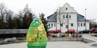 Ilustracja. Wielkanocna pisanka na skwerze Kisiela w Piasecznie, w tle budynek Biura Promocji i Kultury UMiG Piaseczno oraz Centrum Kultury w Piasecznie