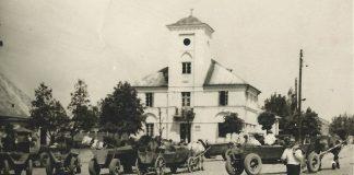 Ilustracja. Historyczna terenowa gra miejska w Piasecznie. Na zdjęciu historyczny rynek przy Ratuszu w Piasecznie.