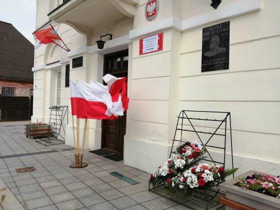 Ratusz z kwiatami, tablicą Józefa Piłsudskiego oraz flagami Polski.