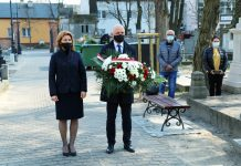 Ilustracja. Piaseczyńskie obchody Miesiąca Pamięci Narodowej kwiecień 2021. Burmistrz Daniel Putkiewicz z wiceburmistrz Hanną Kułakowską-Michalak składają kwiaty przy pomniku pamięci.
