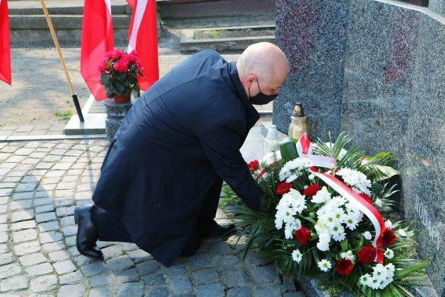 Ilustracja. Piaseczyńskie obchody Miesiąca Pamięci Narodowej kwiecień 2021. Burmistrz Daniel Putkiewicz składa kwiaty przy pomniku pamięci.