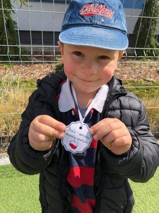 Ilustracja. Na zdjęciu chłopiec trzyma w rękach medal z napisem biało-czerowne zawody sportowe. Chłopiec jest na dworze, ubrany w niebieską czapkę, czarną kurtkę, koszulkę w czerwno-granatową kratę z białym kołnierzykiem. W tle widać ogrodzenie.