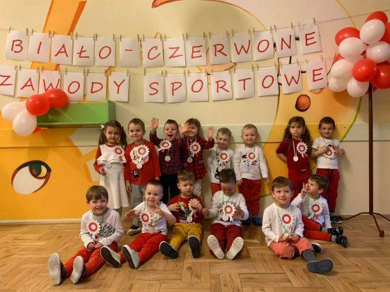 Ilustracja. Na zdjęciu grupa dzieci pozująca do zdjęcia wewnątrz budynku. Na ścianie napis biał-czerowne zawody sportowe i dekoracja z balonów.