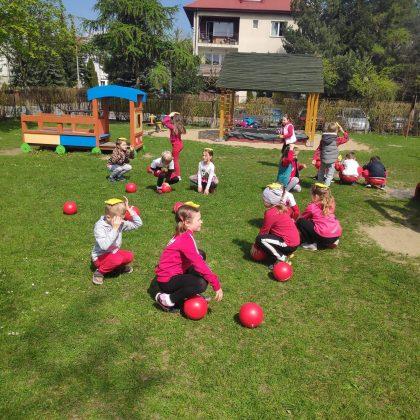 Ilustracja. Grupa dzieci na dworze, na trawniku bierze udział w zawodach sportowych. Dzieci kucają, na głowie trzymają kolorowe woreczki. Pomiędzy nimi leżą czerwone piłki. W tle widać plac zabaw i budynek.
