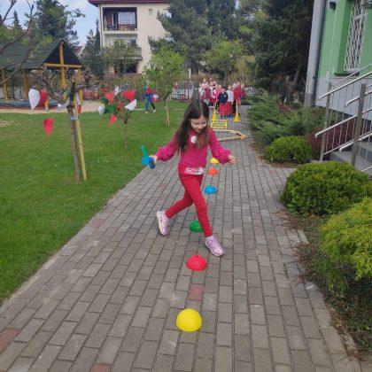 Ilustracja. Na zdjęciu dziewczynka pokonuje slalom ustawiony z kolorowych grzybków sportowych. W tle widać grupę innych dzieci biorących udział w zawodach oraz budynki.