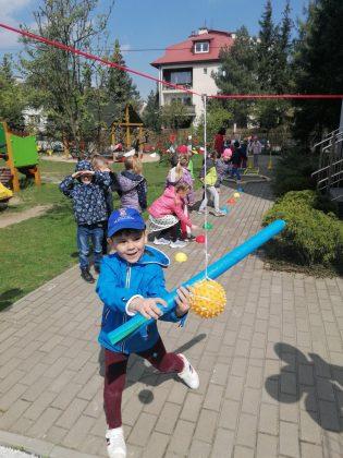 Ilustracja. Na zdjęciu chłopiec trzyma w ręku niebieski makaron piankowy i próbuje zbić podwieszoną żółtą piłkę. W tle inne dzieci biorące udział w zawodach. W oddali widać budynek.