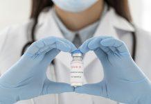 Ilustracja. Lekarz trzyma szczepionkę przeciw COVID-19