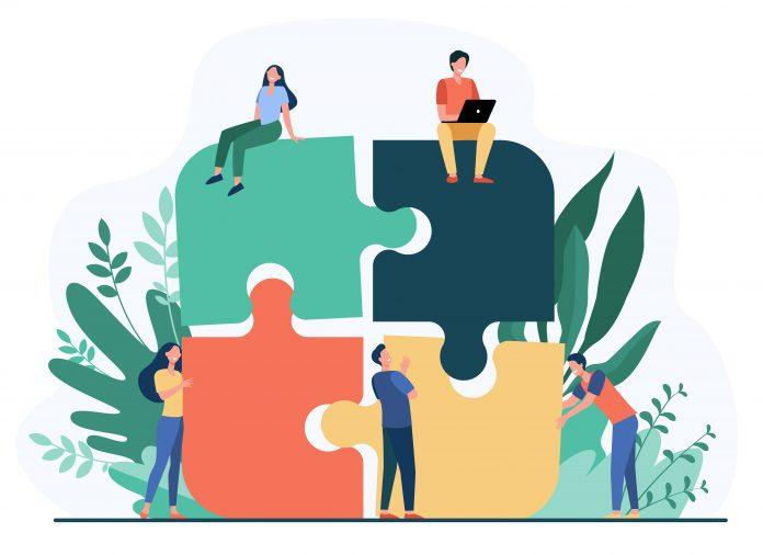 Współpraca. Zespół firmy układanie puzzli na białym tle ilustracji wektorowych płaski. Cartoon partnerów pracujących w związku. Koncepcja pracy zespołowej, partnerstwa i współpracy. Grafika: pch.vector / Freepik
