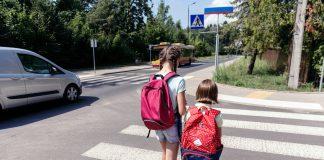 Bezpieczna droga do szkoły. Na zdjęciu dzieci z plecakami idące do szkoły po pasach dla pieszych.