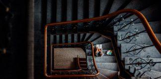 Osoba siedząca na schodach w starym budynku i czytająca książkę. Ujęcie z góry.