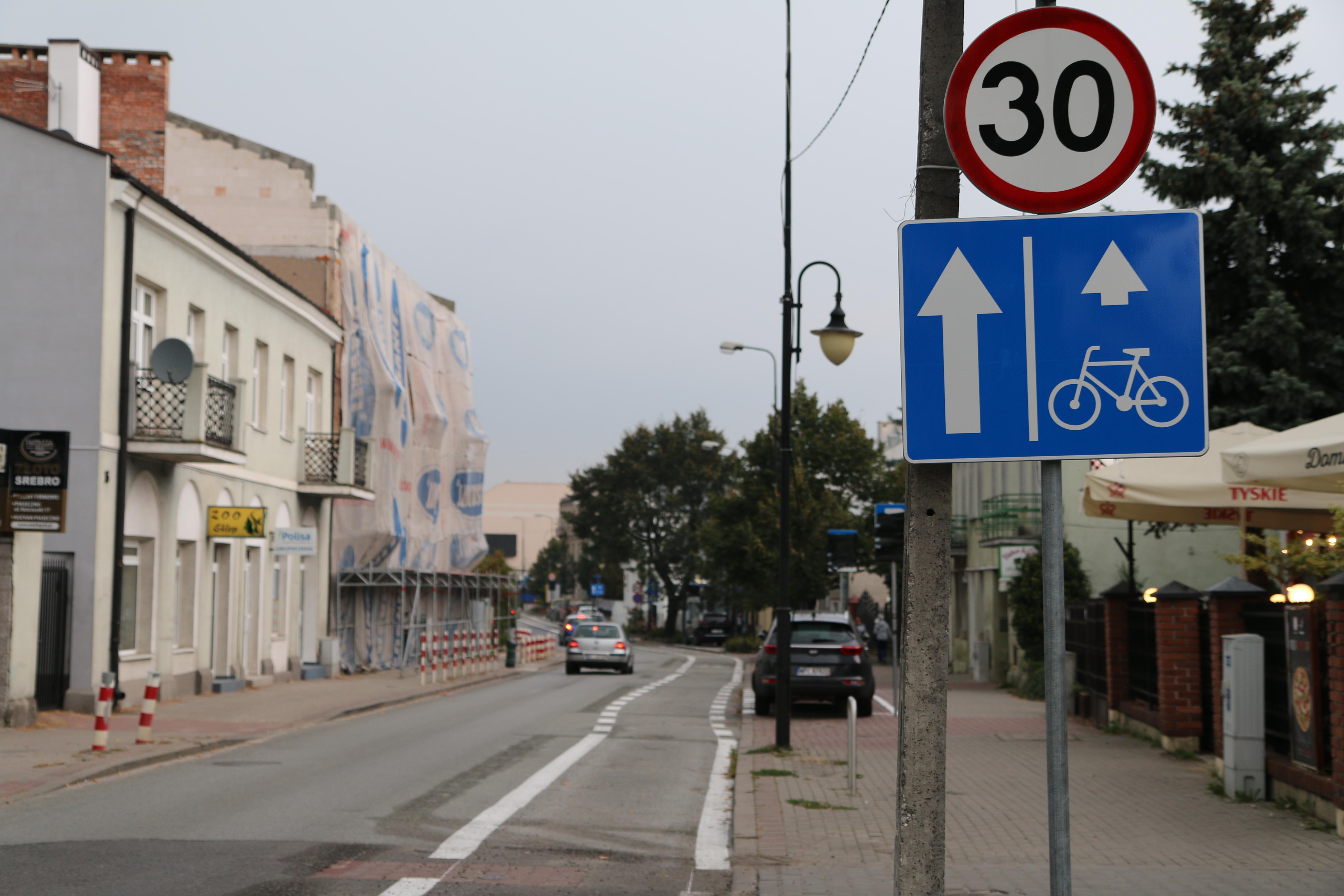 Nowa infrastruktura rowerowa w Piasecznie. Na zdjęciu znaki drogowe z informacją o pasioe rowerowym i pasie ruchu dla samochodów oraz ograniczeniu prędkości do 30 km/h.
