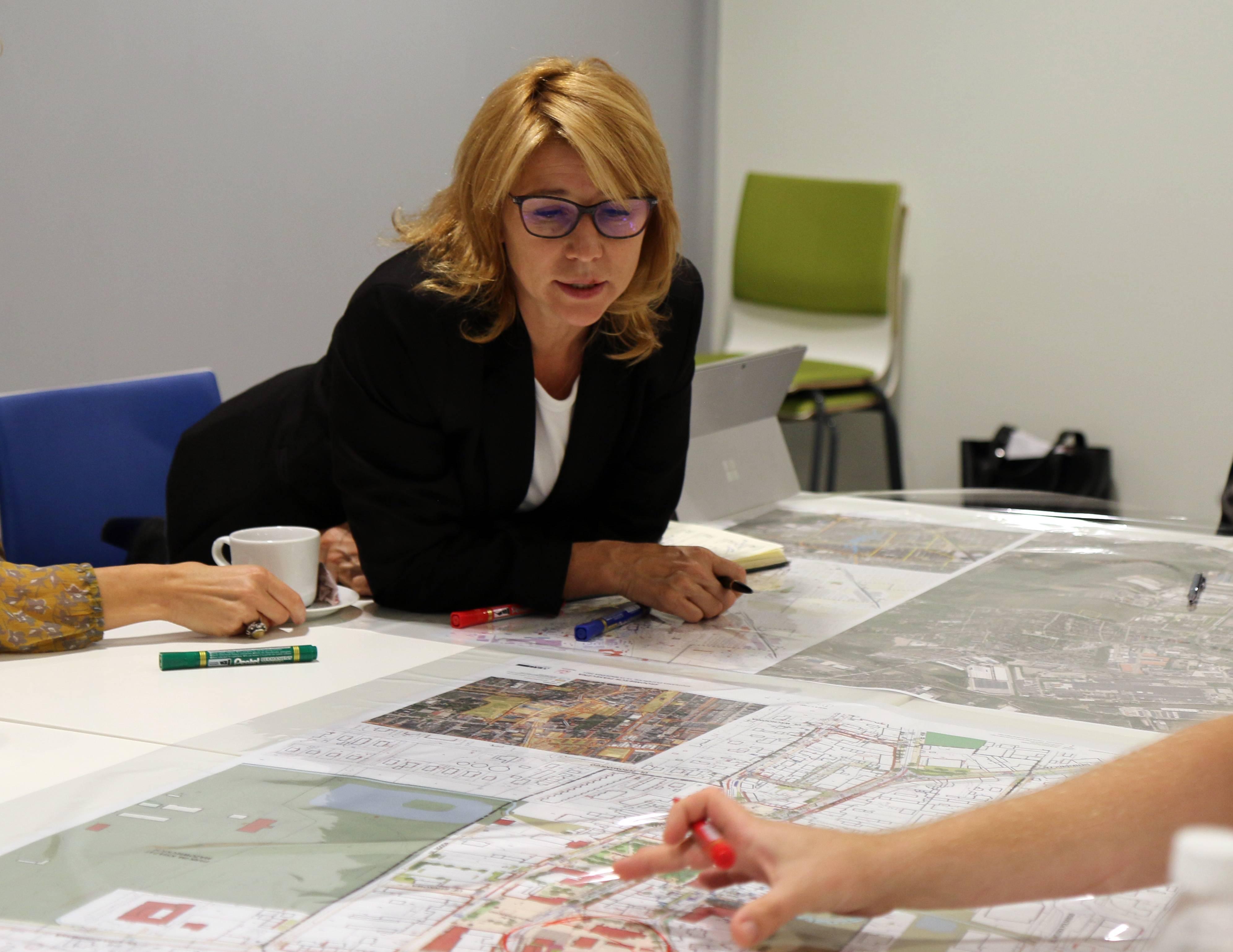 Jakie centrum Piaseczna? Na zdjęciu wiceburmistrz Hanna Kułakowska-Michalak nad stołem z rozłożoną mapą Piaseczna.