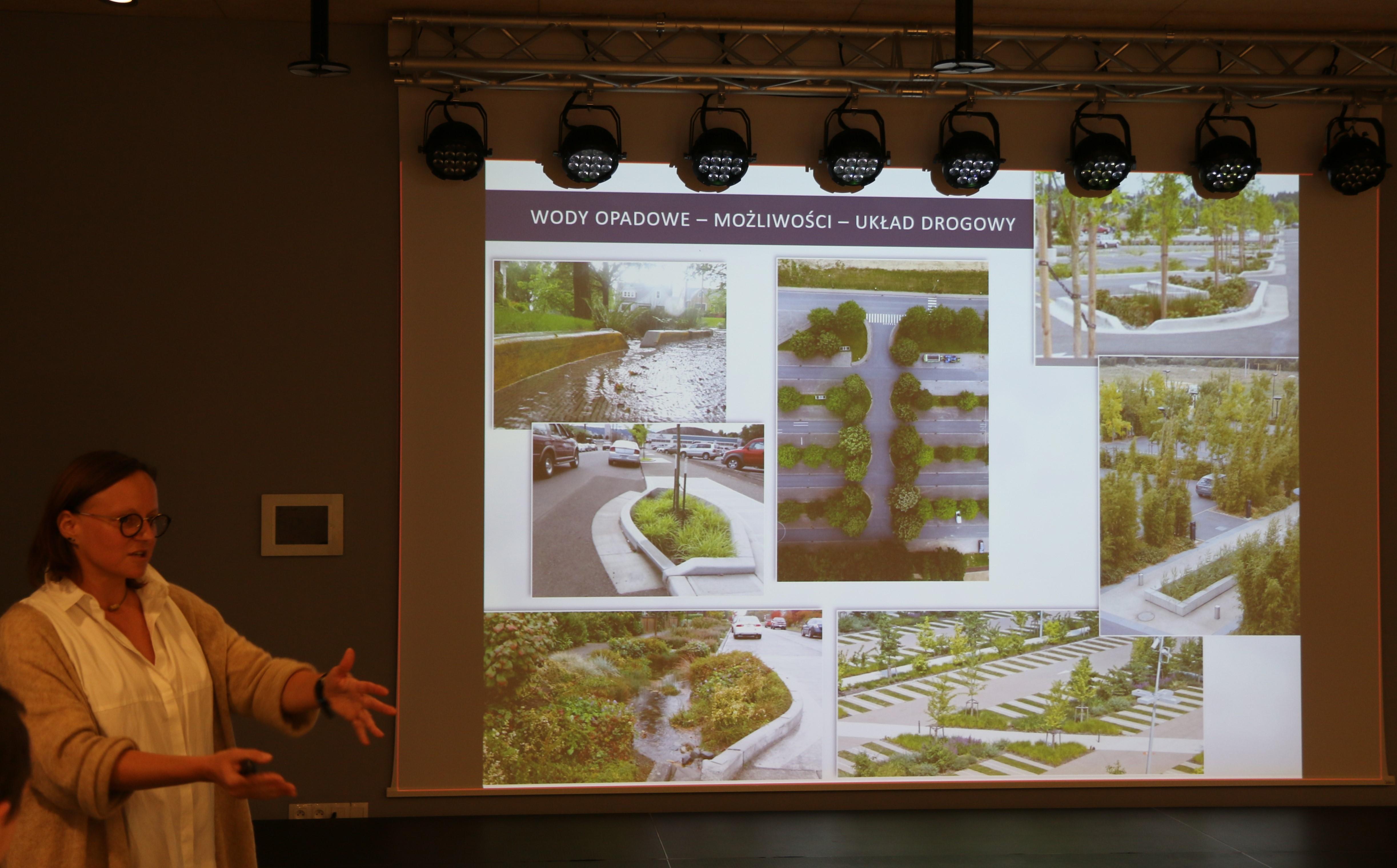 Jakie centrum Piaseczna? Na zdjeciu tablica multimedialna z obrazem rozwiązań infrastruktury deszczowej oraz prelegentka.