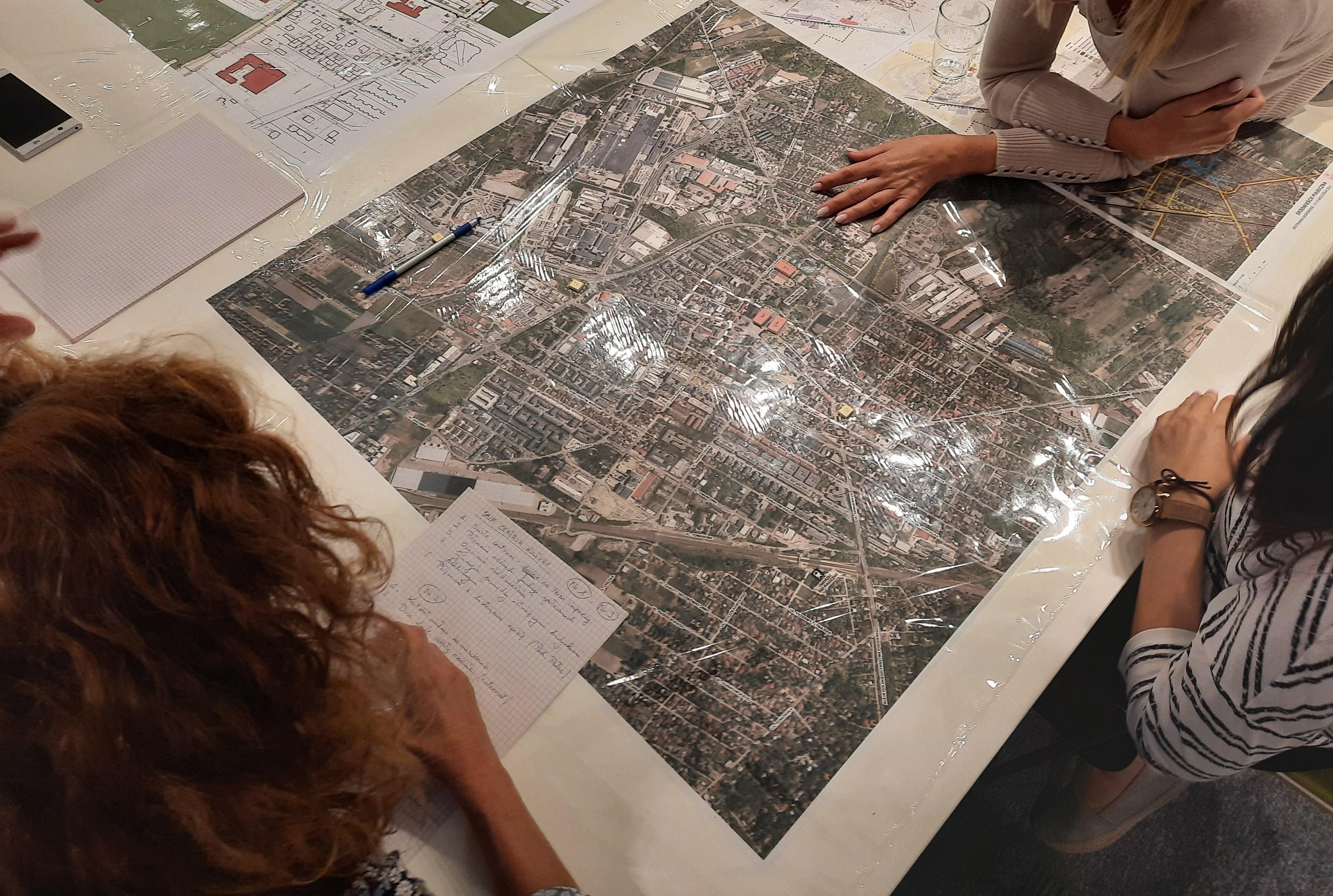 Jakie centrum Piaseczna? Na zdjęciu urzędnicy i rozłożona na stole mapa miasta.