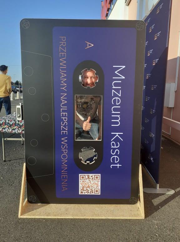 Kwiatek za elektrośmieci. Na zdjęciu ścianka do zdjęć w kształcie kasety magnetofonowej z napisem Muzeum Kaset.