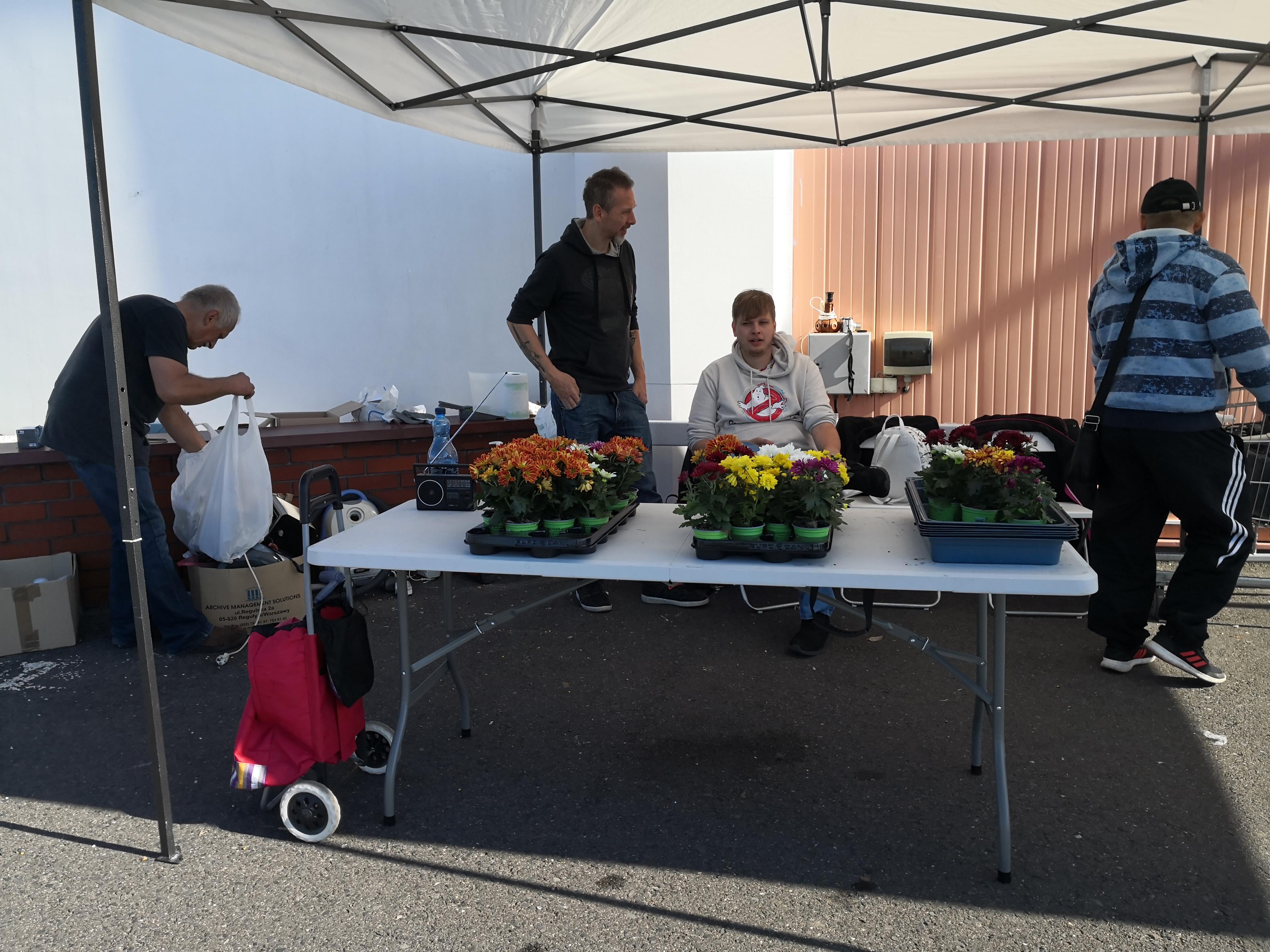 Kwiatek za elektrośmieci. Na zdjęciu organizatorzy akcji przy stoliku z kwiatami doniczkowymi.