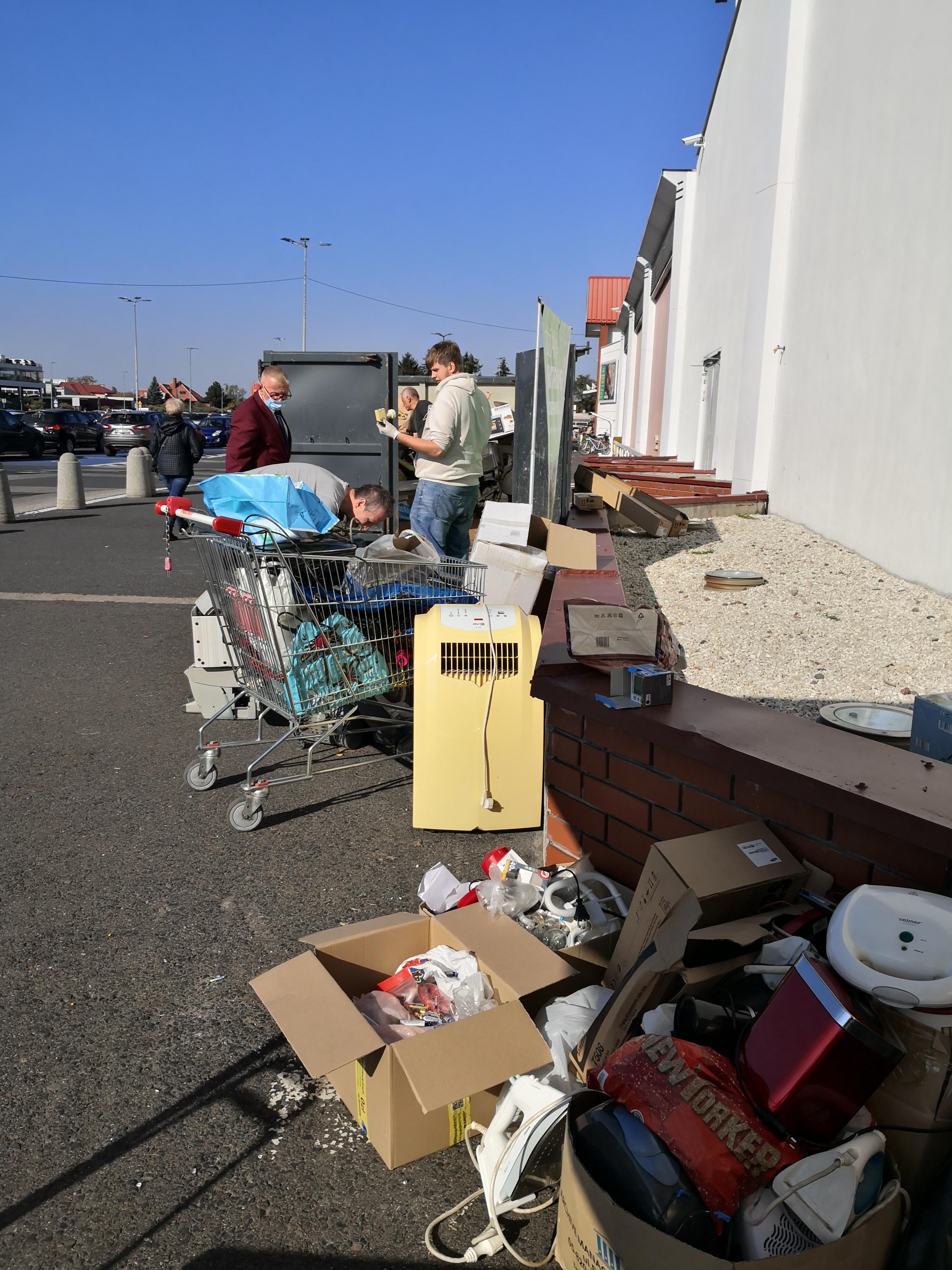 Kwiatek za elektrośmieci. Na zdjęciu kartony i wózek sklepowy wypełnione śmieciami.