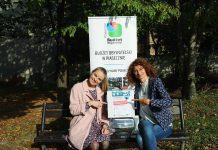 Ilustracja. Losowanie projektów do głosowania Budżet Obywatelski 2022. Koordynatorki Budżetu Obywatelskiego z urną do głosowania. W tle stoi baner promocyjny BO Piaseczno.